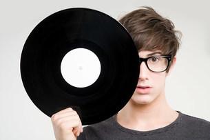 A teenage boy holding a vinyl recordの写真素材 [FYI03470108]