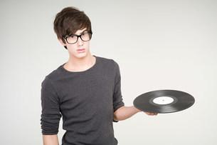 A teenage boy holding a vinyl recordの写真素材 [FYI03470109]