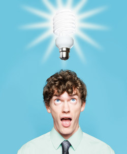 A young man looking at an energy saving lightbulbの写真素材 [FYI03470167]