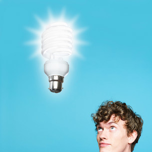 A young man looking at an energy saving lightbulbの写真素材 [FYI03470169]