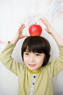 A boy with an apple on his headの写真素材 [FYI03470389]