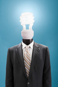 Businessman with energy saving lightbulb as headの写真素材 [FYI03470911]
