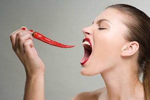Woman biting a red chili pepperの写真素材 [FYI03471116]