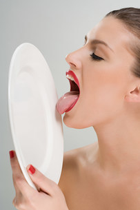Woman licking a plateの写真素材 [FYI03471125]