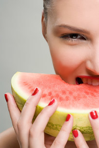 Young woman eating watermelonの写真素材 [FYI03471131]