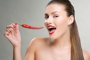 Woman holding a red chili pepperの写真素材 [FYI03471137]