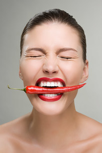 Woman biting a red chili pepperの写真素材 [FYI03471139]