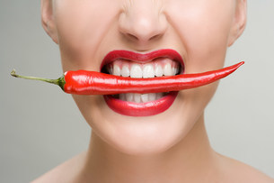 Woman with a red chili pepper between her teethの写真素材 [FYI03471152]