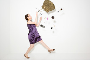 Woman and objects falling out of handbagの写真素材 [FYI03471413]