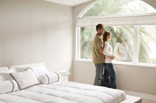 Couple looking out of bedroom windowの写真素材 [FYI03471480]