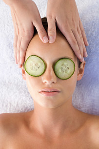 Woman with cucumber slices over eyes receiving massageの写真素材 [FYI03471788]