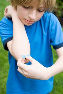 Boy putting plaster on elbowの写真素材 [FYI03472030]