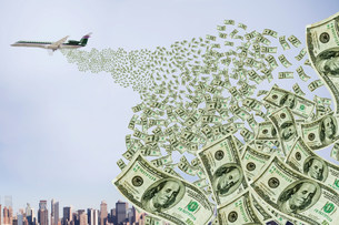 Airplane dropping money over cityのイラスト素材 [FYI03472089]