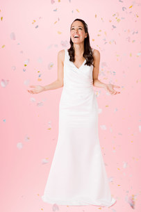 Bride standing beneath falling confettiの写真素材 [FYI03472422]