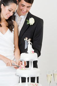 Bride and groom cutting a wedding cakeの写真素材 [FYI03472430]