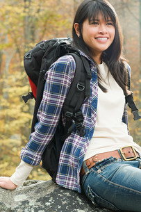 Young woman in forest with backpackの写真素材 [FYI03473054]
