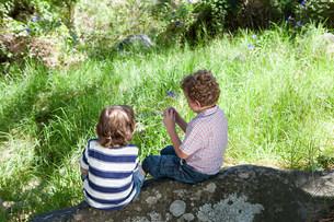 Two boys sitting on a rockの写真素材 [FYI03473655]