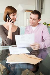 Couple on telephone with billsの写真素材 [FYI03473904]