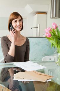 Woman on telephone with billsの写真素材 [FYI03473911]