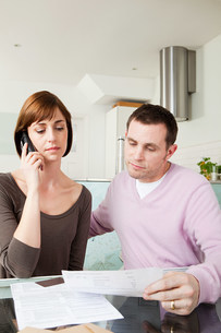 Couple on telephone with billsの写真素材 [FYI03473936]