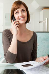 Woman on telephone with billsの写真素材 [FYI03473943]