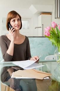 Woman on telephone with billsの写真素材 [FYI03473951]