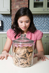 Young woman with cookie jarの写真素材 [FYI03474207]
