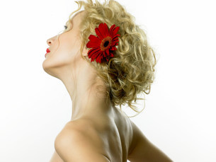 Young woman wearing red flower in hairの写真素材 [FYI03474231]
