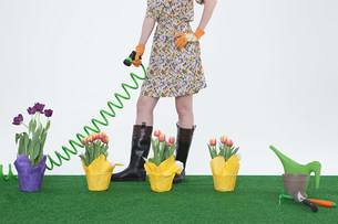 Woman with hose and flowers on artificial turfの写真素材 [FYI03474398]