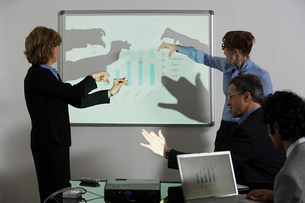 Businesspeople doing shadow puppets in front of whiteboardの写真素材 [FYI03474546]