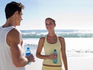 Young couple with bottles of water on beachの写真素材 [FYI03474623]