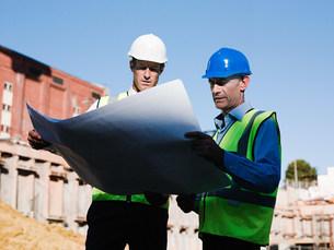 Mature men inspecting blueprints on construction siteの写真素材 [FYI03474714]