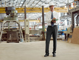 Mature man with clipboard in factoryの写真素材 [FYI03474731]
