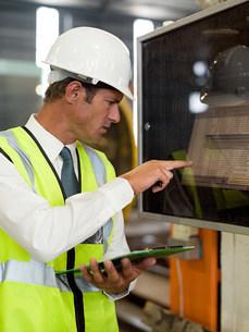 Mature man inspecting factory equipmentの写真素材 [FYI03474735]