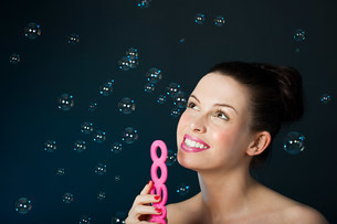 Young brunette woman blowing bubbles with bubble wandの写真素材 [FYI03474765]
