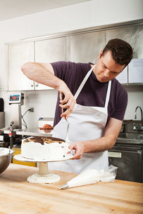 Male chef icing a cake in commercial kitchenの写真素材 [FYI03474806]