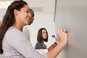 High school students using white boardの写真素材 [FYI03474981]