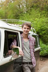 Young man by camper vanの写真素材 [FYI03475066]