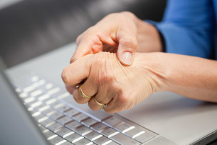Laptop and woman with pain in handの写真素材 [FYI03475157]