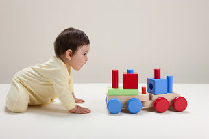 Baby boy playing with toy trainの写真素材 [FYI03475391]