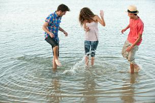Three friends having fun in lakeの写真素材 [FYI03475493]