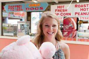 Teenage girl at fun fair with teddy bearの写真素材 [FYI03475706]