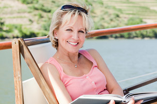 Mature reading book woman on a boat holidayの写真素材 [FYI03475739]