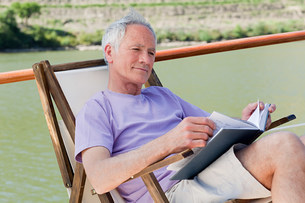 Senior man reading book on a boat holidayの写真素材 [FYI03475758]