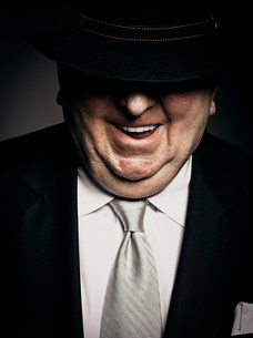 Studio portrait of gangster with hat covering faceの写真素材 [FYI03476070]