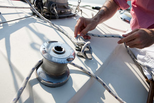 Mid adult man on board yacht holding ropeの写真素材 [FYI03476075]