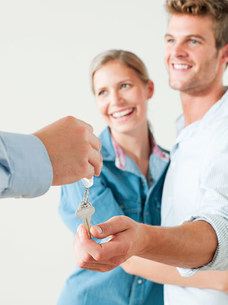 Young couple being handed house keysの写真素材 [FYI03476112]
