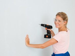 Young woman using electric drillの写真素材 [FYI03476146]