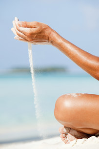 Woman letting sand flow through hands,Maldivesの写真素材 [FYI03476156]