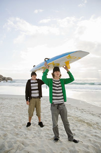 Young men carrying surfboard on headの写真素材 [FYI03476438]